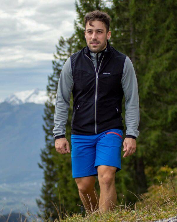 Wandern in den Outdoorshorts Shorty in blau mit orangem Reißverschluss und dem Softshellgilet Tambo an der Schuttannen, Hohenems.